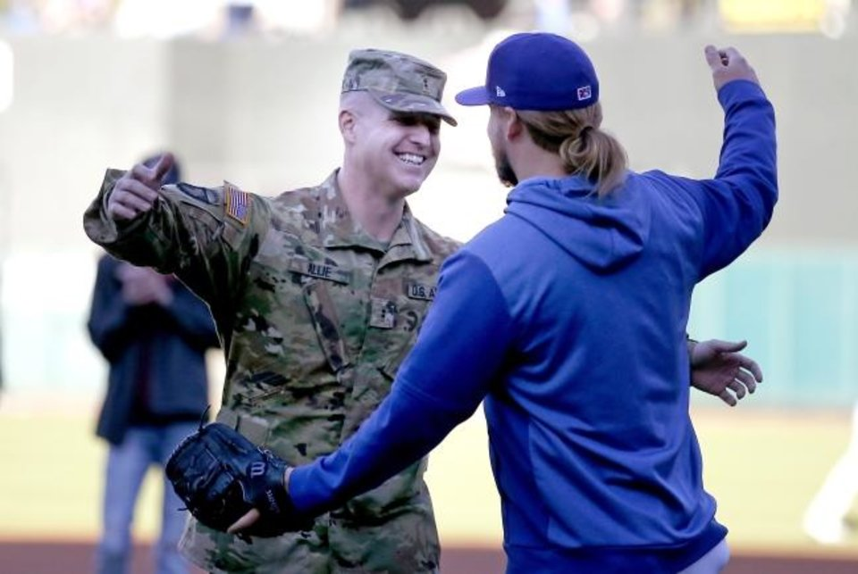 Photo -  Chief Warrant Officer 2 Logan Allie, left, hugs his brother, Oklahoma City Dodgers pitcher Stetson Allie, before Friday night's game against Iowa Cubs at Chickasaw Bricktown Ballpark. Logan, who is back from an eight-month deployment, threw out the first pitch to his brother. [Sarah Phipps/ The Oklahoman]