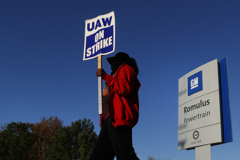 Photo -  Yolanda Jacobs, a United Auto Workers member, walks the picket line at the General Motors Romulus Powertrain plant in Romulus, Mich. [AP PHOTO]