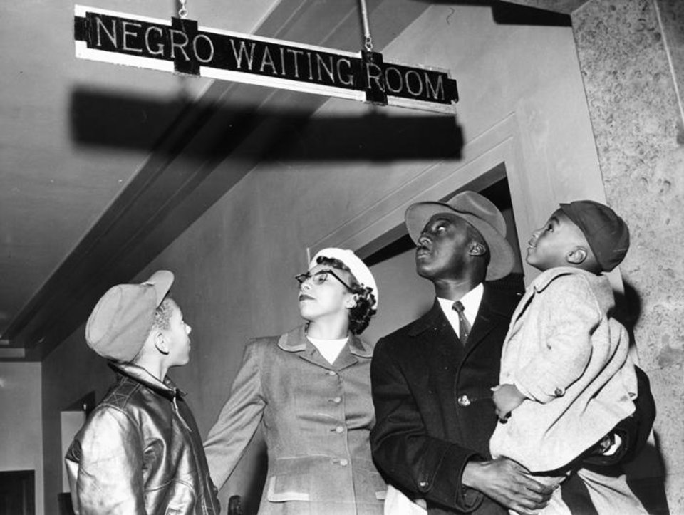 "Photo -  Dr. and Mrs. Charles N. Atkins and their children, Edmond, 10, and Charles, 3, look at a sign that reads ""Negro waiting room"" in 1955 in Oklahoma City. Oklahoman Archive"