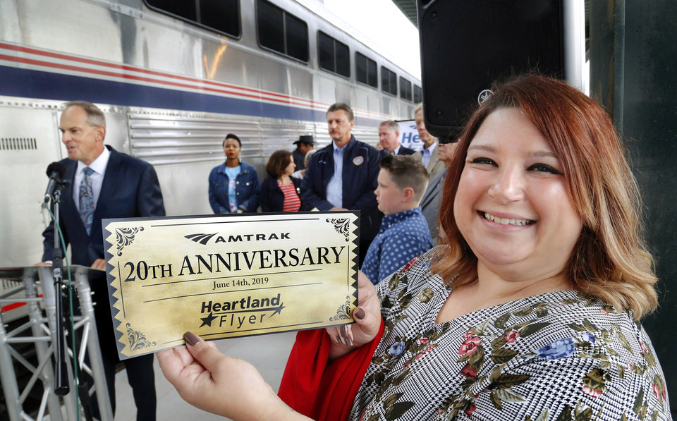 "Photo - Katie Moore shows the ""golden ticket"" presented to her during the ceremony marking the 20th anniversary  of the return of passenger rail service to Oklahoma at Santa Fe Depot in downtown Oklahoma City Friday morning, June 14, 2019. The Heartland Flyer is celebrating its 20th year of serving passengers in Oklahoma and Texas.  The Oklahoma City woman was honored at the celebration as being the person who suggested the name, Heartland Flyer, in 1999 when she was 11 years old. Her family attended the event with her. The Heartland Flyer, which runs daily, has carried more than 1.4 million passengers between Oklahoma City and Fort Worth during the past two decades. Originating its route on Oklahoma City, the Heartland Flyer connects to the Texas Eagle train in Fort Worth, which provides service to major cities including Dallas, Little Rock, St. Louis or Austin and San Antonio. [Jim Beckel/The Oklahoman]"
