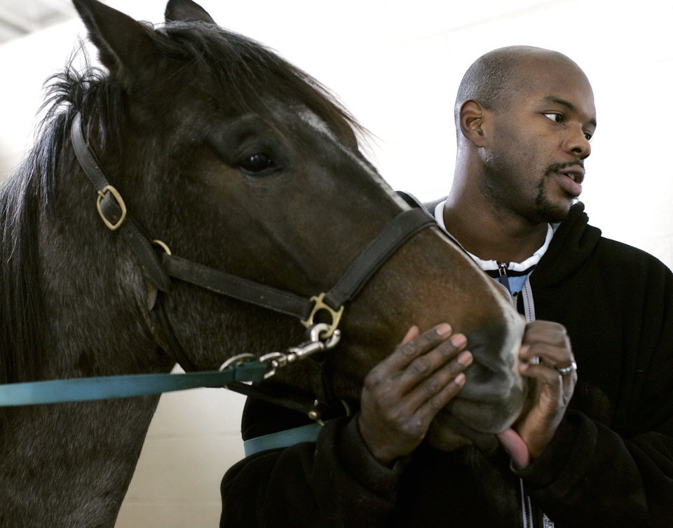Photo - New Orleans/Oklahoma City Hornets NBA basketball player Marc Jackson gets a kiss from Big Bug Hancock at the stables where the horses are kept as Jackson talks about the horses he owns in Edmond, Okla., Saturday, Jan. 20, 2007. By John Clanton, The Oklahoman ORG XMIT: KOD