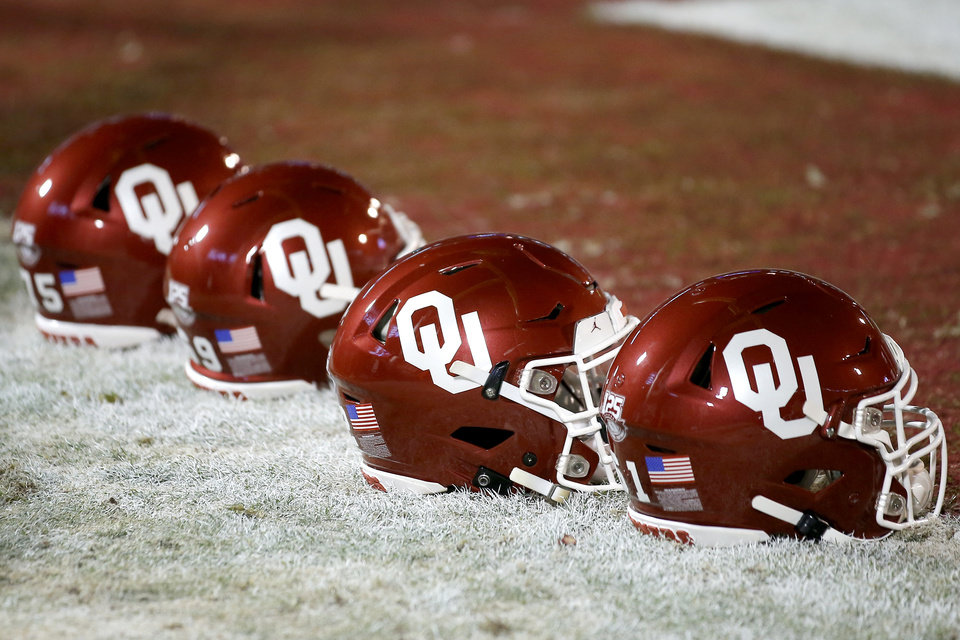 Photo - Helmets sit on the field before an NCAA football game between the University of Oklahoma Sooners (OU) and the TCU Horned Frogs at Gaylord Family-Oklahoma Memorial Stadium in Norman, Okla., Saturday, Nov. 23, 2019. Oklahoma won 28-24. [Bryan Terry/The Oklahoman]