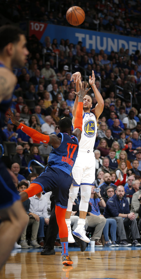 Photo - Stephen Curry (30) shoots over Oklahoma City's Dennis Schroder (17) during the NBA basketball game between the Oklahoma City Thunder and the Golden State Warriors at Chesapeake Energy Arena,  Saturday, March 16, 2019. Photo by Sarah Phipps, The Oklahoman