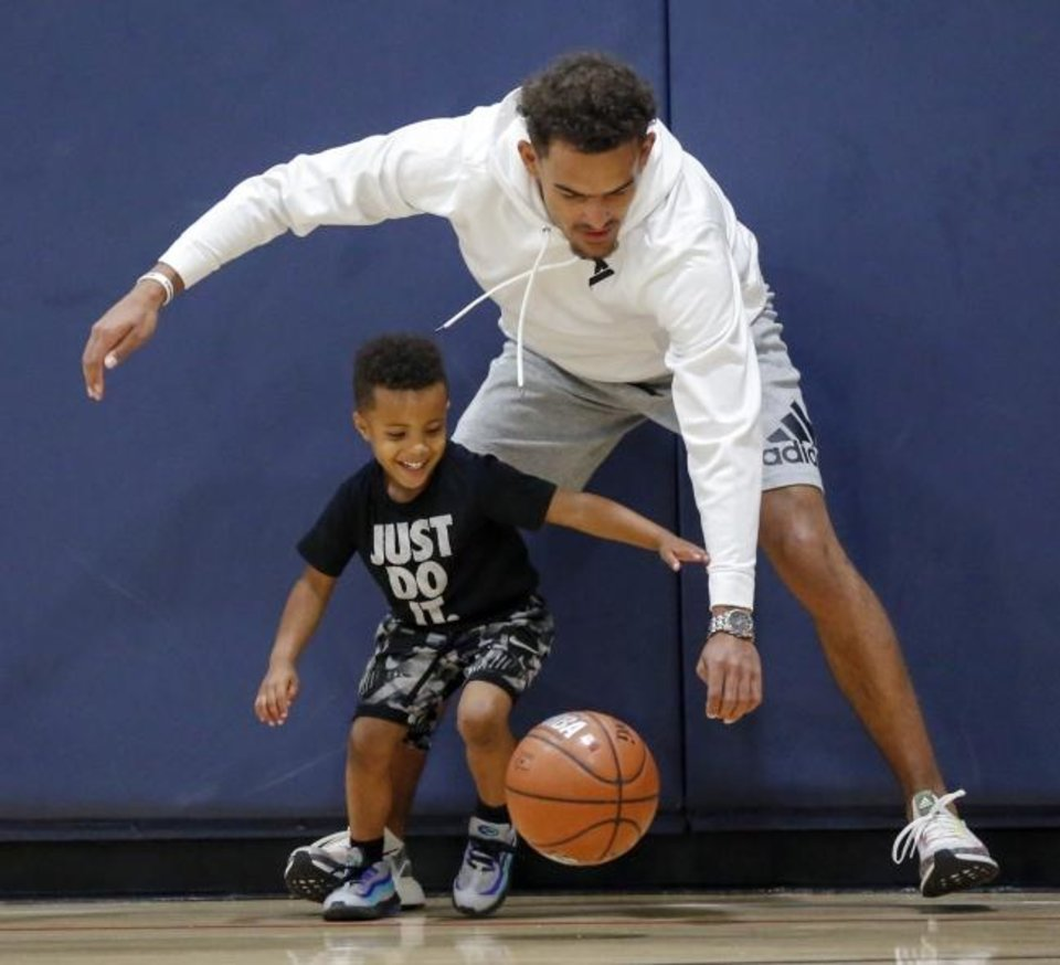 Photo -  Atlanta guard Trae Young dribbles the ball with Drayton Berry, 4, during his youth basketball camp at the Santa Fe Family Life Center in Oklahoma City on Saturday. [Nate Billings/The Oklahoman]