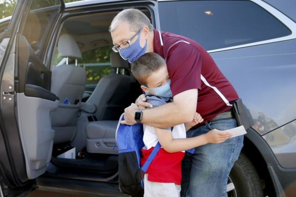 Photo -  Steven Christy hugs his 6-year-old son, Conner Christy, as he drops him off Thursday for his first day of first grade at Charles Haskell Elementary School.  [Bryan Terry/The Oklahoman]