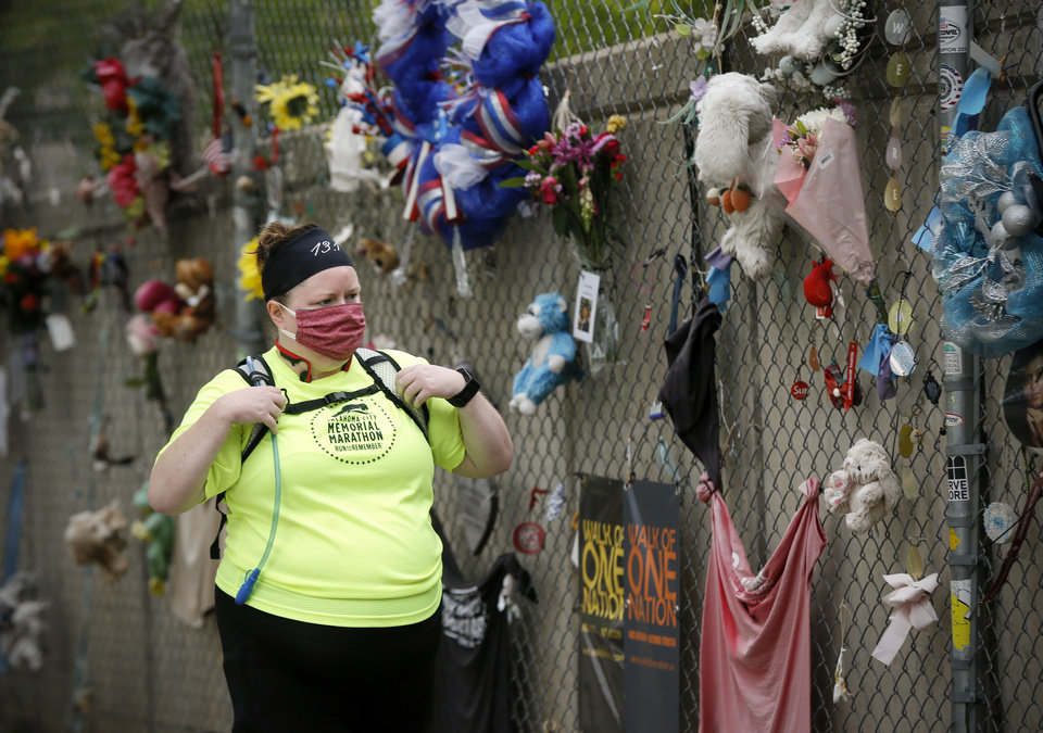 Photo - Holley Mangham looks at the fence outside the Oklahoma City National Memorial and Museum before walking for 168 minutes to honor victims on the 25th anniversary of the bombing of the Alfred P. Murrah Federal Building, in Oklahoma City, Sunday, April 19, 2020. Mangham had planned to run the half marathon in the Oklahoma City Memorial Marathon, which would have taken place the next week and is now postponed. The memorial remains closed and did not hold a live remembrance ceremony because of the coronavirus pandemic. [Nate Billings/The Oklahoman]