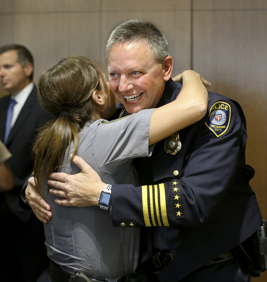 "Photo - New Oklahoma City Police Chief Wade Gourley is hugged by a female officer at police headquarters Monday, July 8, 2019, after a news conference where he was introduced by City Manager Craig Freeman as the new chief. Officers waited in line to greet the new chief and wish him well in his new position. Gourley has been an Oklahoma City police officer for 30 years and was serving as one of the police department's four deputy chiefs before being promoted to chief. He succeeds former Police Chief Bill Citty, who retired in May after 15 years as head of the department.  Freeman said ""Chief Gourley fits the mold of what we're looking for: he's open, honest, innovative and experienced, and he will lead by example. I'm confident he will lead our police department to continue to serve and protect all residents in a fair and equitable manner.""  Gourley is Oklahoma City's 50th chief. He will oversee the 1,235 uniformed officers and 304 other staff members in the police department.  [Jim Beckel/The Oklahoman]"