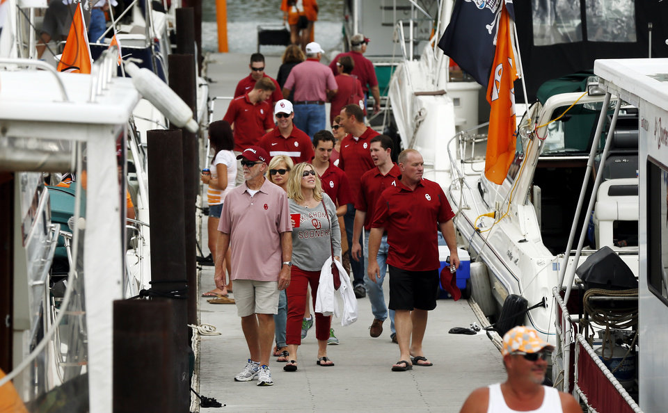 Photo - OU and Tennessee fans walk among boats of the Vol Navy along the Tennessee River before the college football game between the Oklahoma Sooners and the Tennessee Volunteers at Neyland Stadium in Knoxville, Tennessee, Saturday, Sept. 12, 2015. Photo by Nate Billings, The Oklahoman