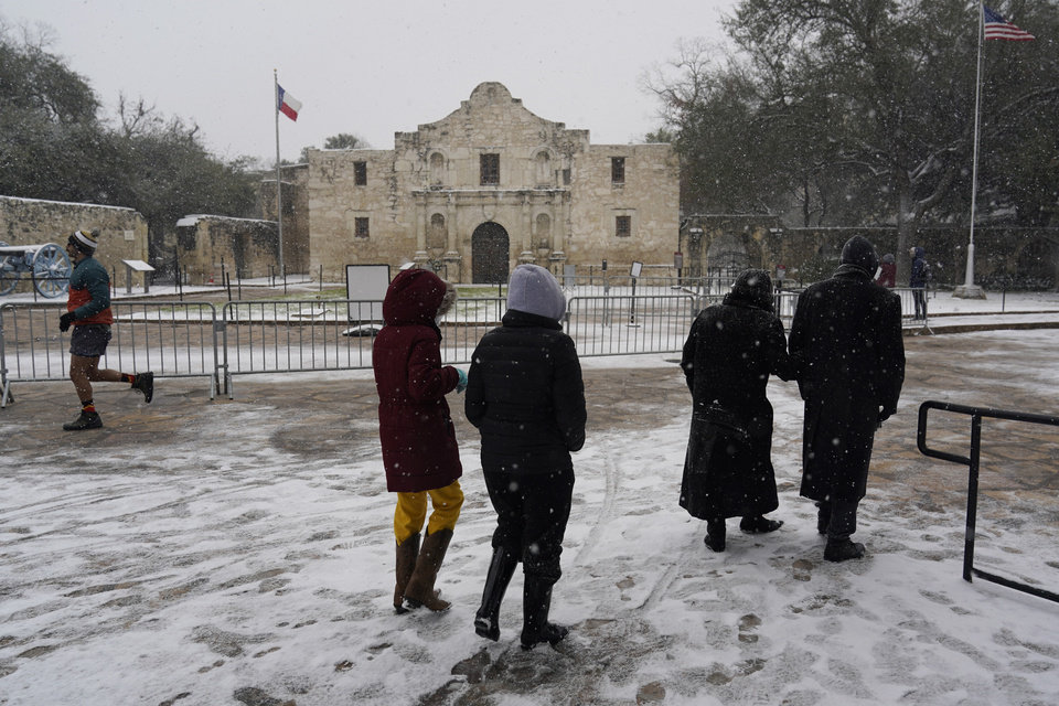 Photo -  People walk through the snow as they pass the Alamo, Thursday, Feb. 18, 2021, in San Antonio. Snow, ice and sub-freezing weather continue to wreak havoc on the state's power grid and utilities. (AP Photo/Eric Gay)