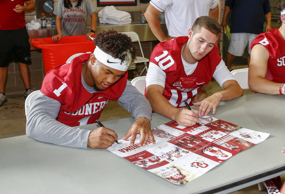 Photo - Oklahoma Quarterbacks Kyler Murray (1) and Austin Kendall (10) autograph posters for football fans during fan and media day at The Gaylord Family Oklahoma Memorial Stadium in Norman, Okla. on Saturday, Aug. 6, 2016. (Photo by Alonzo J. Adams for the Oklahoman)