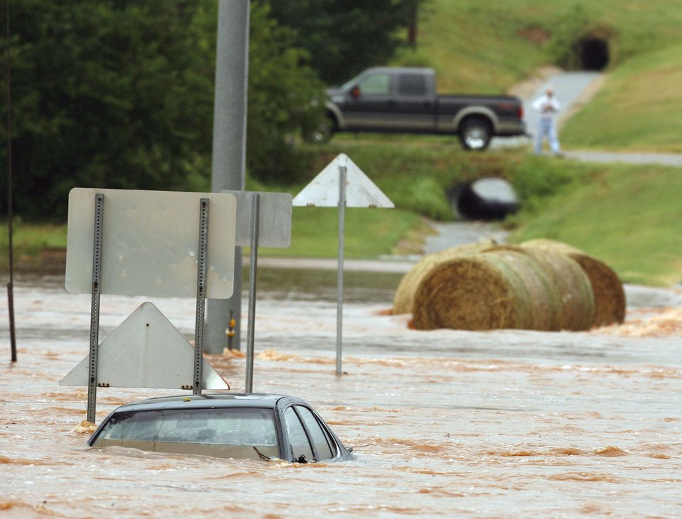 Photo - A car is full of water at Franklin Road and N.E. 24th after flooding in Norman, Oklahoma on Sunday, August 19, 2007.  A policeman on the scene was unaware of the condition of location of the driver.   BY STEVE SISNEY, THE OKLAHOMAN