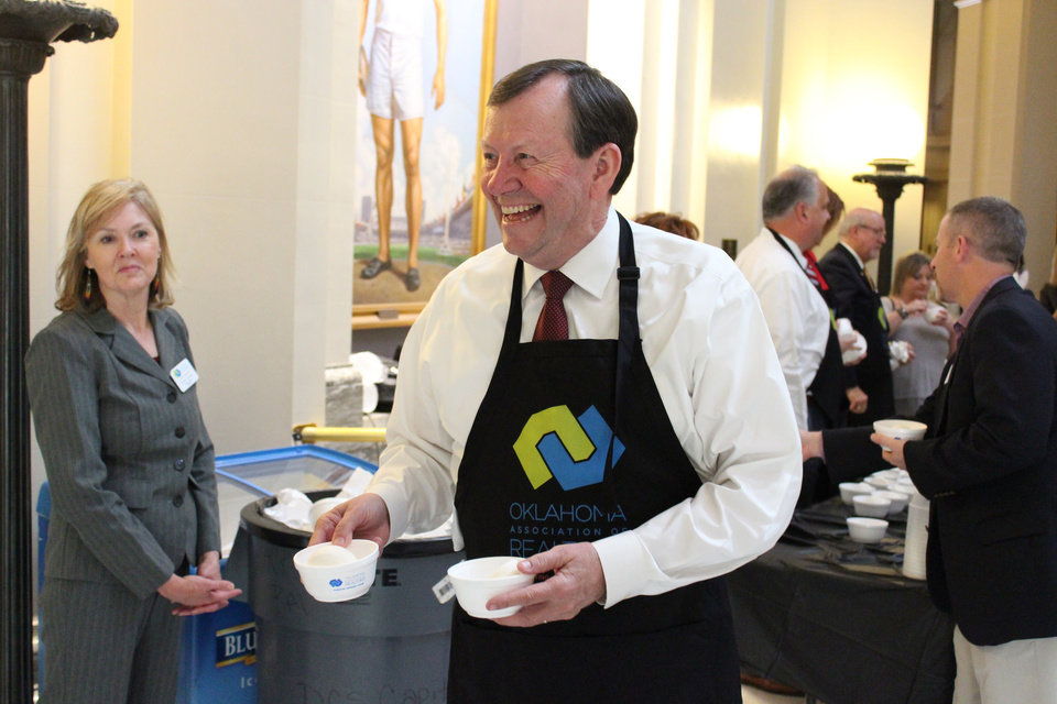 Photo -  Susan Conway, left, Oklahoma Association of Realtors member services specialist, watches Chuck Harris of Oklahoma City, president of the Oklahoma Association of Realtors, serving coffee at Real estate Day at the Capitol April 6. [PHOTO PROVIDED BY OKLAHOMA ASSOCIATION OF REALTORS]