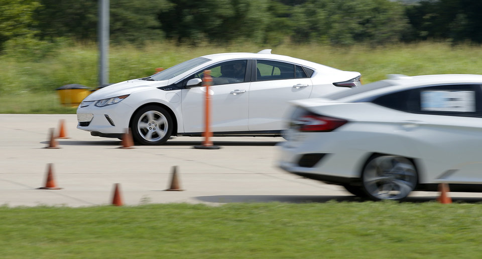 Photo -  A driver takes a Chevrolet Volt through a course set up at Oklahoma State University-Oklahoma City's precision driving course on Saturday. People were allowed to test drive electric vehicles during Oklahoma Gas and Electric's Electric Vehicle Ride and Drive event. [Photos by Bryan Terry, The Oklahoman]