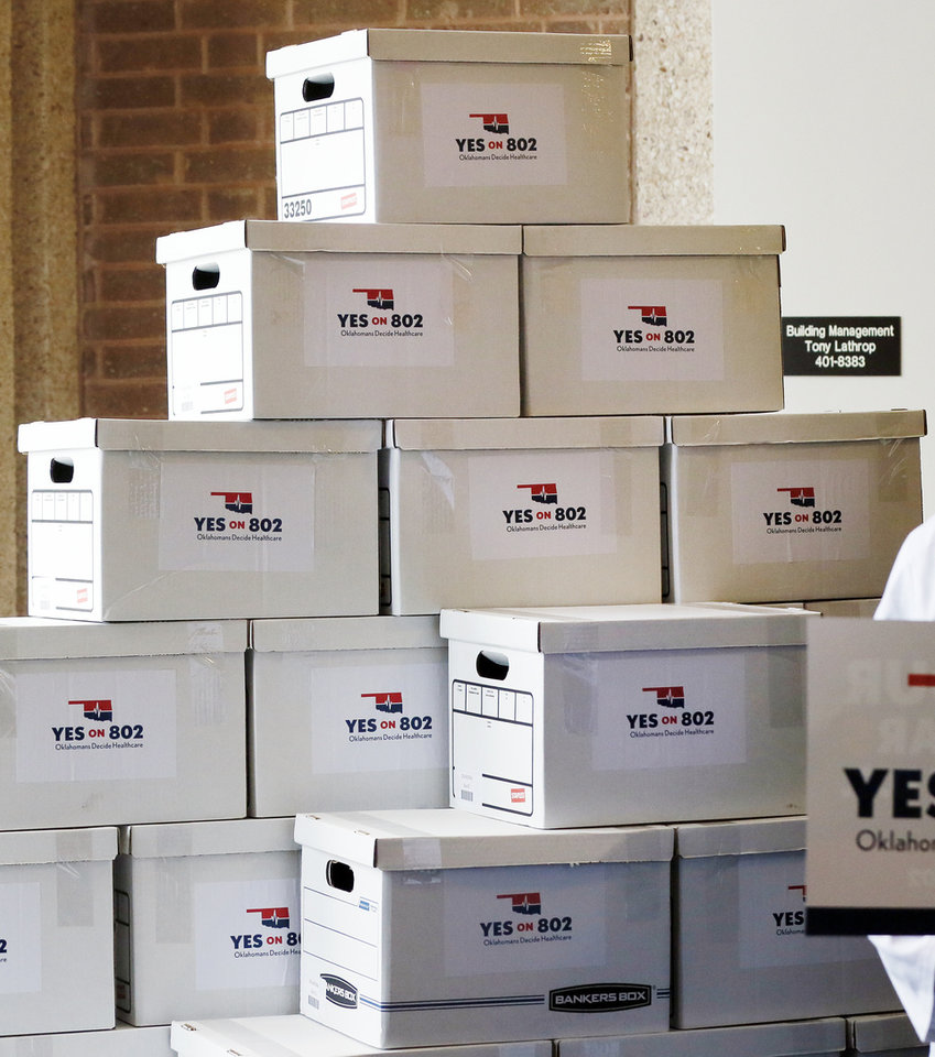 Photo - Boxes of petitions for state question 802 to put Medicaid expansion on the ballot are stacked in the lobby before being delivered to the Oklahoma Secretary of State's office in Oklahoma City, Thursday, Oct. 24, 2019. [Nate Billings/The Oklahoman]