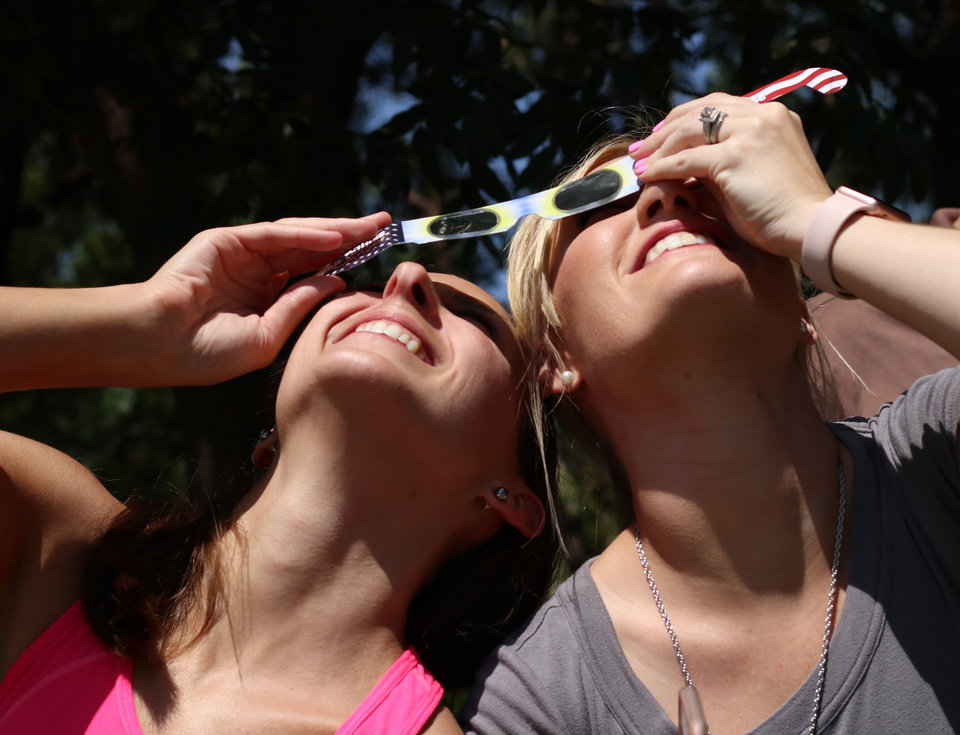 Photo -  Rachel Olsen, left, and her co-worker at Devon, Kayla Young, share a pair of glasses to view the eclipse during the great American solar eclipse party Monday on the Great Lawn of the Myriad Botanical Gardens. [Photo by Doug Hoke, The Oklahoman]