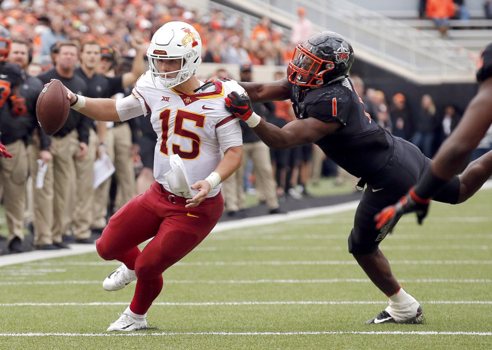 Photo - Oklahoma State's Calvin Bundage (1) ties to bring down Iowa State's Brock Purdy (15) in the third quarter during a college football game between the Oklahoma State Cowboys (OSU) and the Iowa State Cyclones at Boone Pickens Stadium in Stillwater, Okla., Saturday, Oct. 6, 2018. Iowa State won 48-42. Photo by Sarah Phipps, The Oklahoman