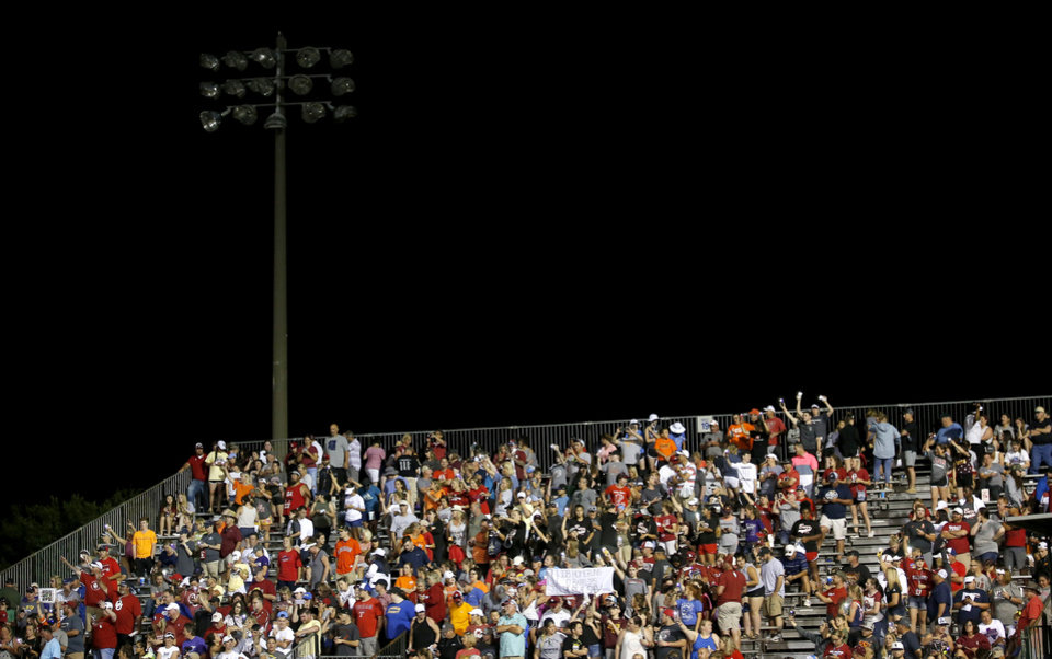 Photo - Fans cheer after the right field light went out during a Women's College World Series between Oklahoma State (OSU) and Oklahoma at USA Softball Hall of Fame Stadium in Oklahoma City,  Friday, May 31, 2019.  [Sarah Phipps/The Oklahoman]