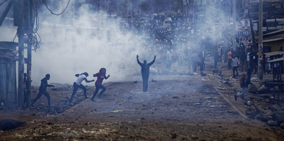 Image result for A man seeking safety walks with his hands in the air through a thick cloud of tear gas towards riot police as they clash with protesters throwing rocks in the Kawangware slum of Nairobi, Kenya, on Aug. 10, 2017.
