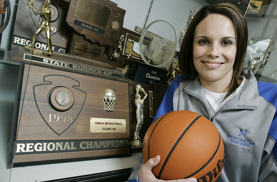Photo - Newcastle girls basketball coach Casi Bays poses at the trophy case at Newcastle High school Thursday, Feb. 1, 2007. She is leading Newcastle into state tournament contention for the first time since she played at the school. BY JACONNA AGUIRRE/THE OKLAHOMAN. ORG XMIT: KOD