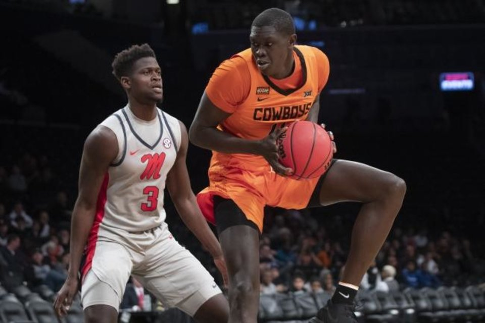 Photo -  Oklahoma State forward Yor Anei, right, drives against Mississippi forward Khadim Sy on Friday in New York. [AP Photo/Mary Altaffer]