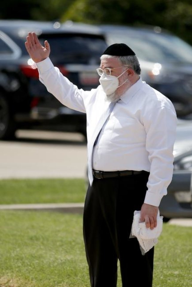 Photo -  Rabbi Ovadia Goldman directs traffic during a drive-thru mask giveaway event at Chabad Community Center for Jewish Life and Learning, 3000 W Hefner Road. [Sarah Phipps/The Oklahoman]