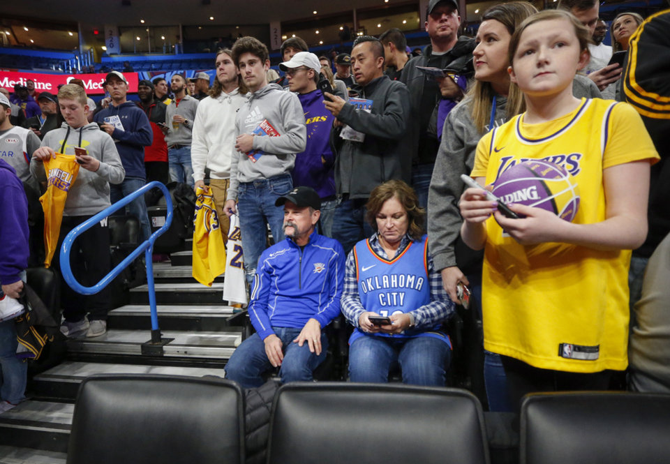 Photo - Thunder fans Mat Brainerd and Kathy Brained sit in their seats as they are surrounded by fans of the Lakers waiting to get autographs more than an hour before an NBA basketball game between the Oklahoma City Thunder and the Los Angeles Lakers at Chesapeake Energy Arena in Oklahoma City, Friday, Nov. 22, 2019. [Nate Billings/The Oklahoman]