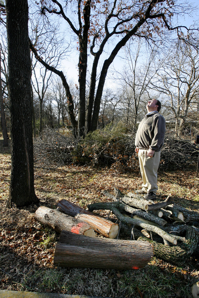 Photo - Michael Johnson, owner of Horticultural Solutions Inc., standing between cut tree limbs and a pile of downed limbs in the Arrowhead Hills housing addition in Edmond Wednesday, Jan. 9, 2008. BY PAUL B. SOUTHERLAND, THE OKLAHOMAN ORG XMIT: KOD