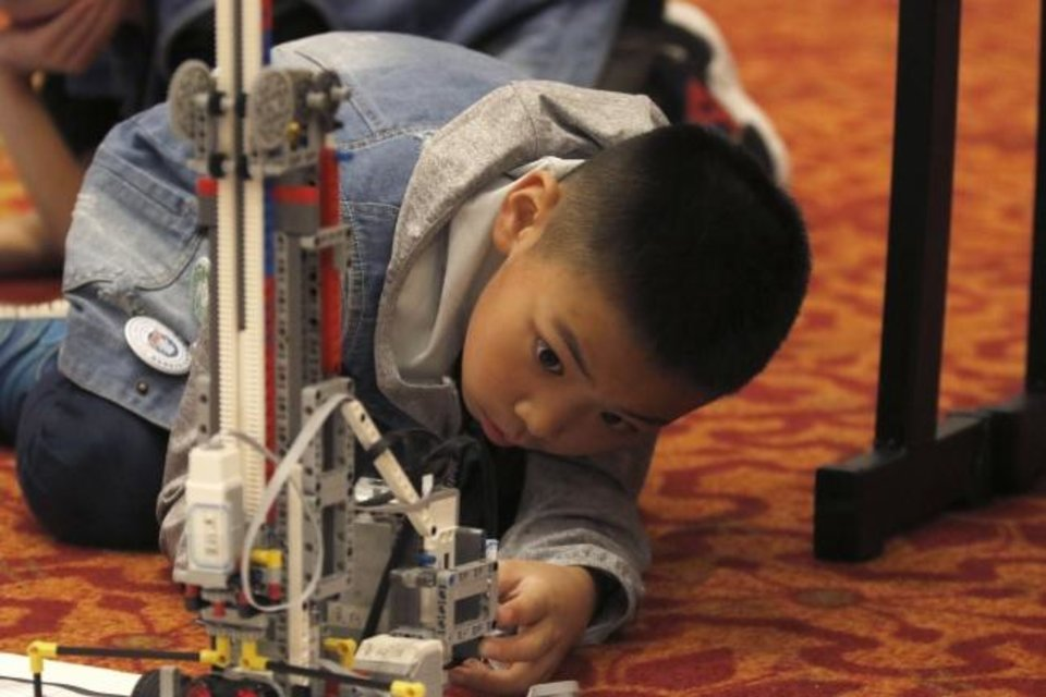 Photo -  Yuhang Zhang, a member of Maker Planets 1704, works Monday on the team's robot at the Global Conference on Educational Robotics in Norman. [PAXSON HAWS/THE OKLAHOMAN]