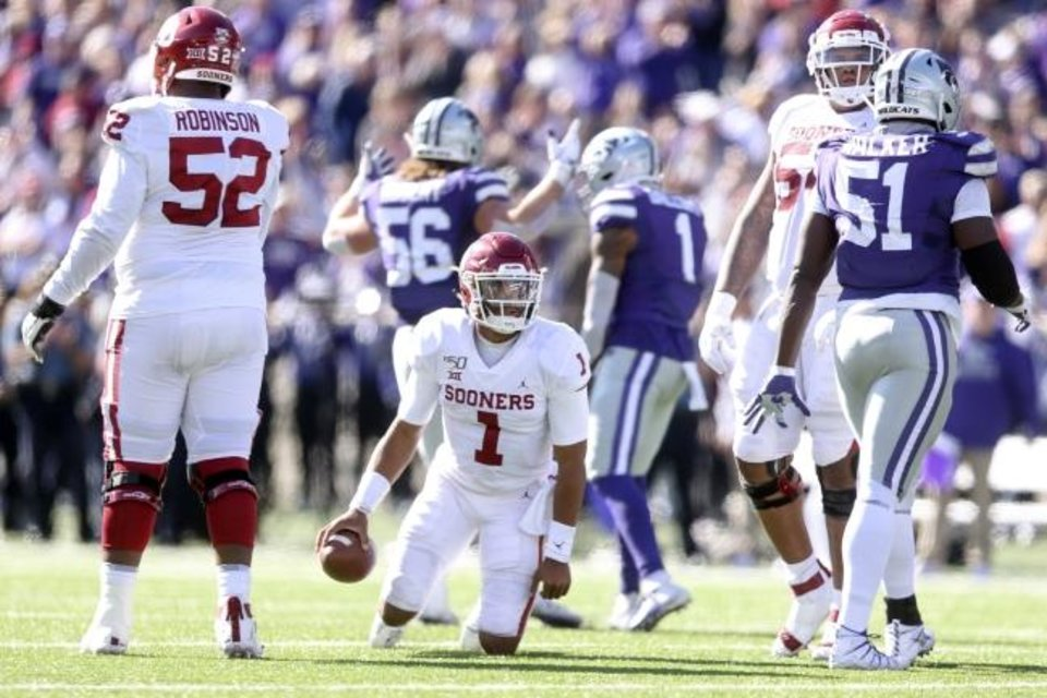 Photo -  Kansas State defensive end Wyatt Hubert (56) and linebacker Eric Gallon II (1) celebrate as Oklahoma quarterback Jalen Hurts (1) picks himself up off the ground during Saturday's game in Manhattan, Kan. [Ian Maule/Tulsa World via AP]