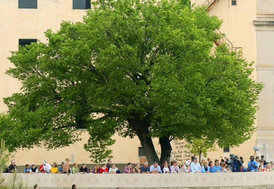 Photo - In this 2005 photo, people gather under the Survivor Tree during a ceremony marking the 10th anniversary of the Alfred P. Murrah Federal Building bombing. The tree is on the grounds of the Oklahoma City National Memorial in downtown Oklahoma City. [Oklahoman Archives]