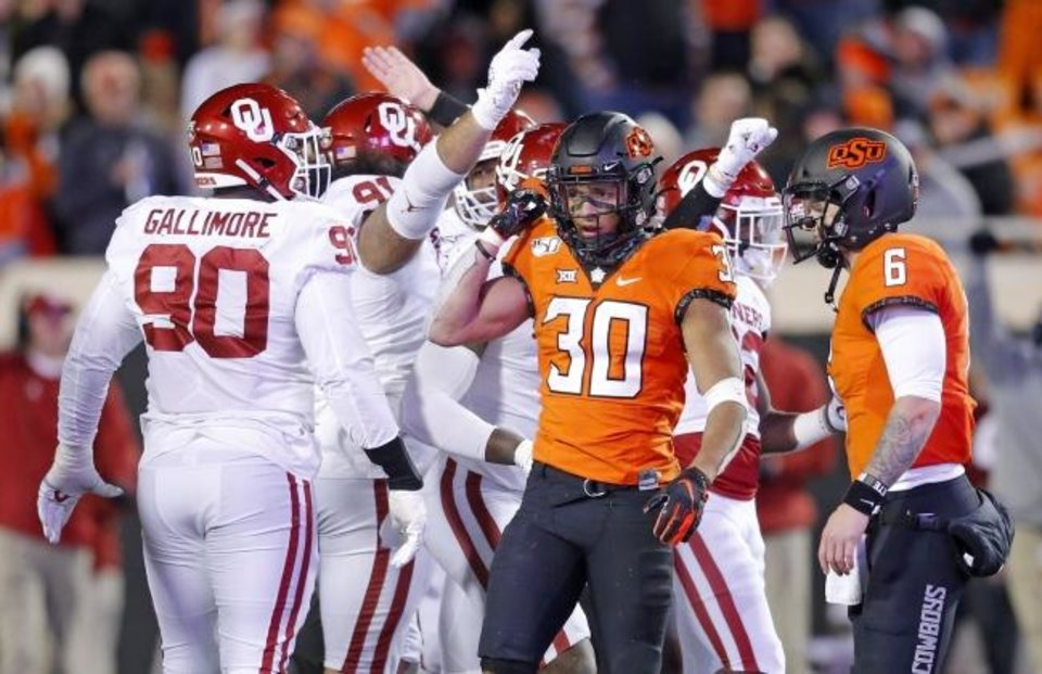 Photo -  Oklahoma's defense celebrates a stop as Oklahoma State running back Chuba Hubbard (30) and quarterback Dru Brown (6) walk off the field in the fourth quarter Saturday in Stillwater. [Sarah Phipps/The Oklahoman]
