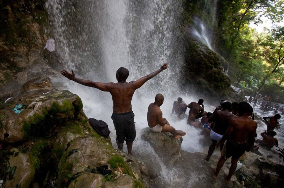 Photo -  Voodoo pilgrims bathe in a waterfall believed to have purifying powers during an annual pilgrimage in Saut d' Eau, Haiti, Saturday July 16, 2011. The annual pilgrimage to Saut d' Eau venerates the site where believers say the Virgin Mary, whom many here revere as the goddess of love, Ezili Danto, once appeared.  (AP Photo/Eduardo Verdugo)