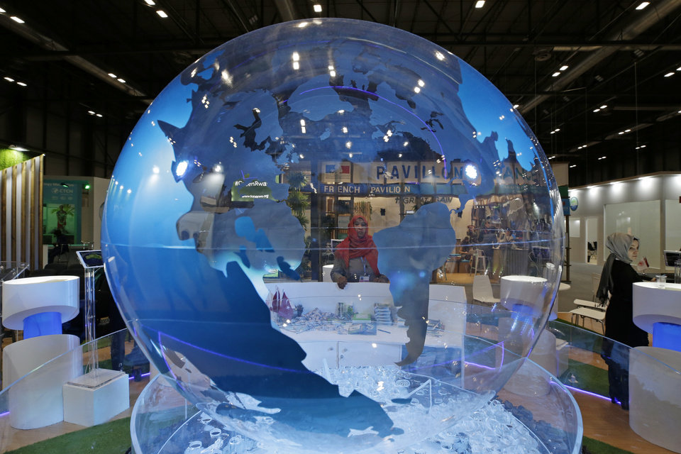 Photo -  A woman looks at a World globe at the COP25 climate talks congress in Madrid, Spain, Friday, Dec. 13, 2019. Officials from almost 200 countries are scrambling to reach an agreement at a United Nations climate meeting amid growing concerns that key issues may be postponed for another year. (AP Photo/Paul White)