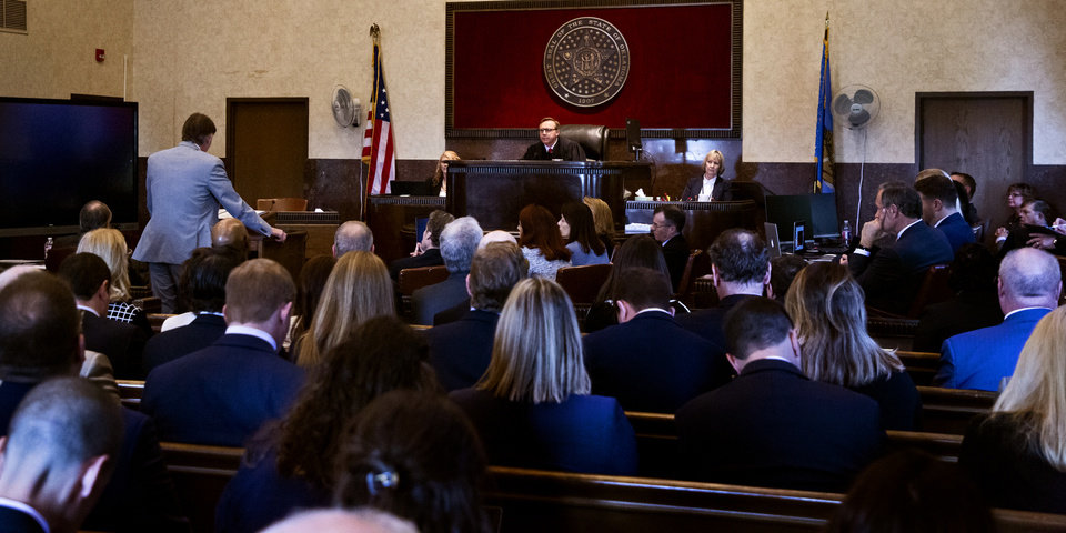 Photo - Judge Thad Balkman listens to Attorney General Mike Hunter speak during opening statements during the opioid trial at the Cleveland County Courthouse in Norman, Okla. on Tuesday, May 28, 2019. The proceeding are the first public trial to emerge from roughly 2,000 U.S. lawsuits aimed at holding drug companies accountable for the nationÕs opioid crisis.  [Chris Landsberger/The Oklahoman]