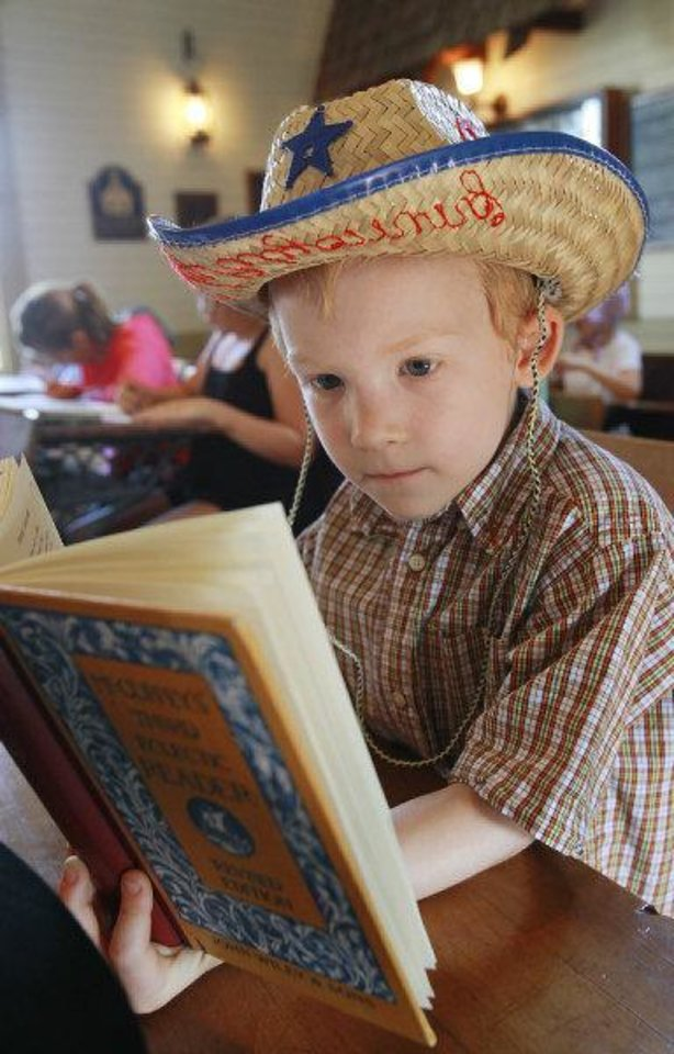 Photo - Scott Sims, 6, reads from his McGuffey's reader Wednesday during 1889 Summer Camp at Edmond's historic school house. PHOTO BY DAVID MCDANIEL, THE OKLAHOMAN  David McDaniel