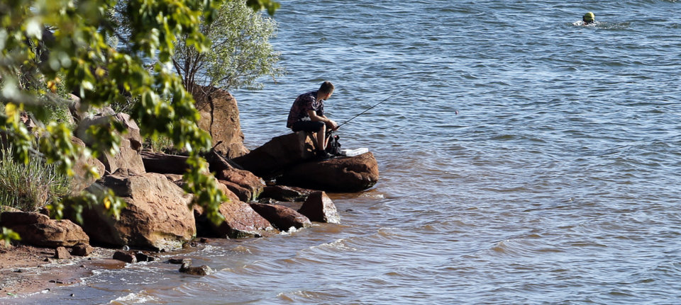 Photo -  A man fishes from the rocks at Lake Thunderbird. Fishing is a popular pastime in Oklahoma, but the state Department of Environmental Quality says people should be cognizant of the amount of fish they eat from some Oklahoma lakes. [PHOTO BY STEVE SISNEY, THE OKLAHOMAN]