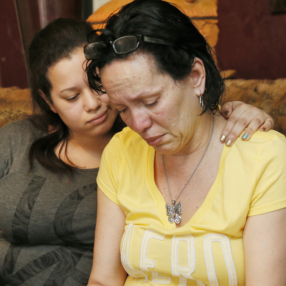 Photo -  Nair Rodriguez, right, and her daughter Luinahi Rodriguez comfort each other during a 2014 interview about the death of husband and father Luis Rodriguez during an incident with Moore police at the Warren Theatre. The two are at the Rodriguez family's home in Norman. [Photo by Nate Billings, The Oklahoman Archives]