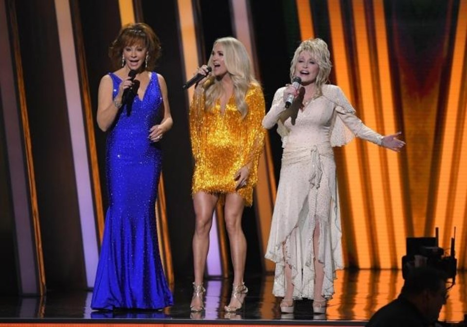 Photo -  Hosts Reba McEntire, left, Carrie Underwood and Dolly Parton appear Wednesday at the 53rd annual CMA Awards at Bridgestone Arena in Nashville, Tenn. [AP Photos]