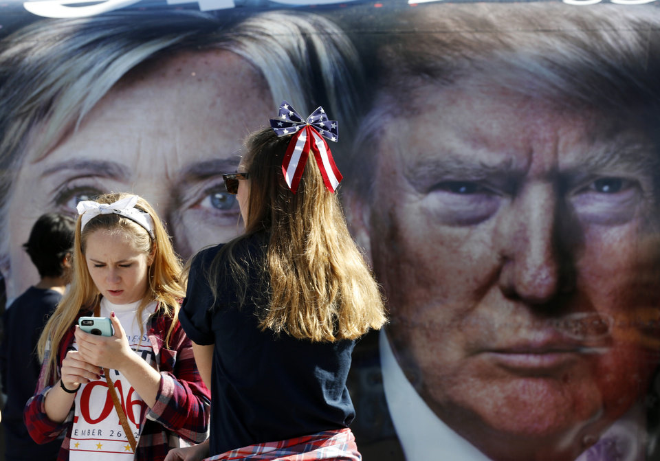 Photo - People pause near a bus adorned with large photos of candidates Hillary Clinton and Donald Trump before the presidential debate at Hofstra University in Hempstead, N.Y., Monday, Sept. 26, 2016. (AP Photo/Mary Altaffer)
