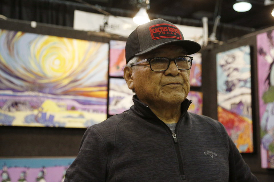 Photo - Baje Whitehorne Sr. talks with a reporter and shows his art work at the first day of the 2019 Red Earth Festival at the Cox Convention Center in Oklahoma City, Oklahoma Friday, June 7, 2019.  [Paxson Haws/The Oklahoman]
