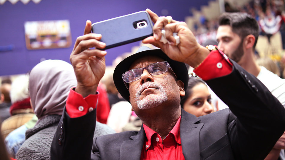 Photo - Ronald Shelton takes a photo of the Oklahoma for Warren sign during an Elizabeth Warren campaign stop in Oklahoma City at Northwest Classen High School, her alma mater, Sunday, December 22, 2019. [Photo by Doug Hoke/The Oklahoman]