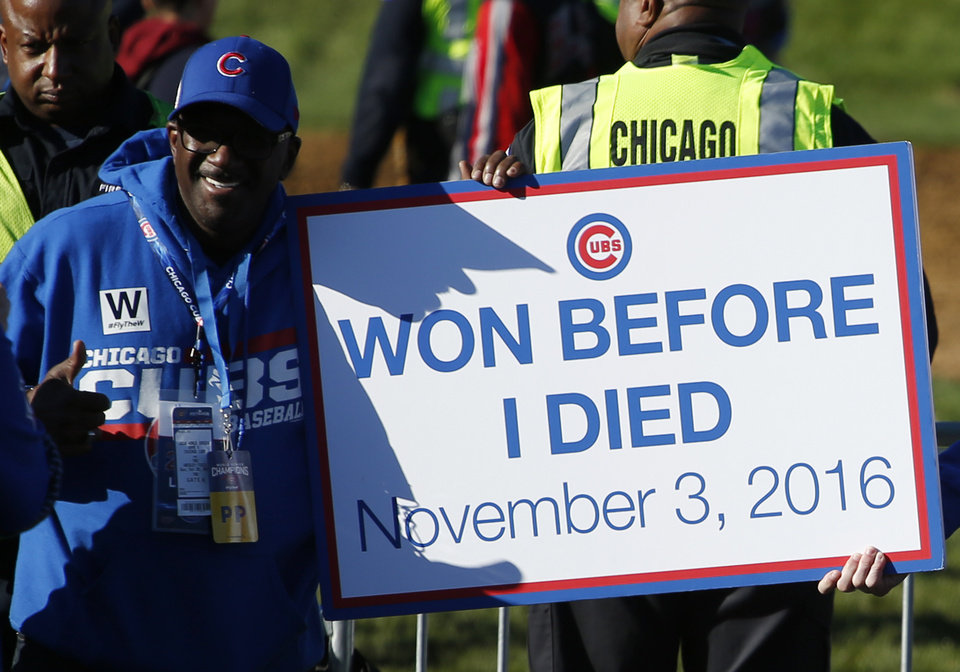 Photo - A Chicago Cubs fan holds a sign as he celebrates at a rally in Grant Park honoring the World Series baseball champions in Chicago, Friday, Nov. 4, 2016. (AP Photo/Nam Y. Huh)