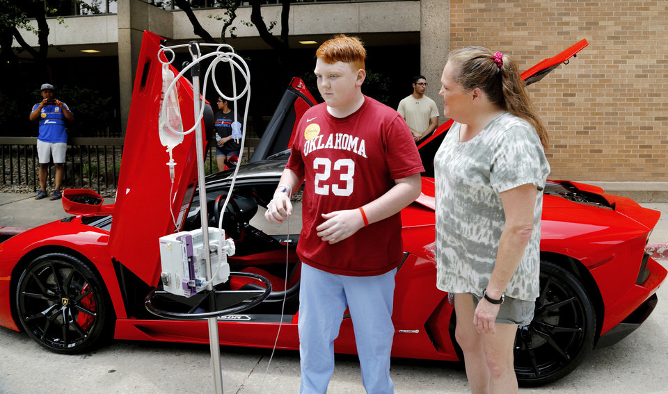 Photo - A patient leaves this sports car and walks to another one, just a few feet away. Redline4Kids is a new nonprofit that helps connect kids in the hospital with a chance to see cool cars. Photo by Jim Beckel, The Oklahoman