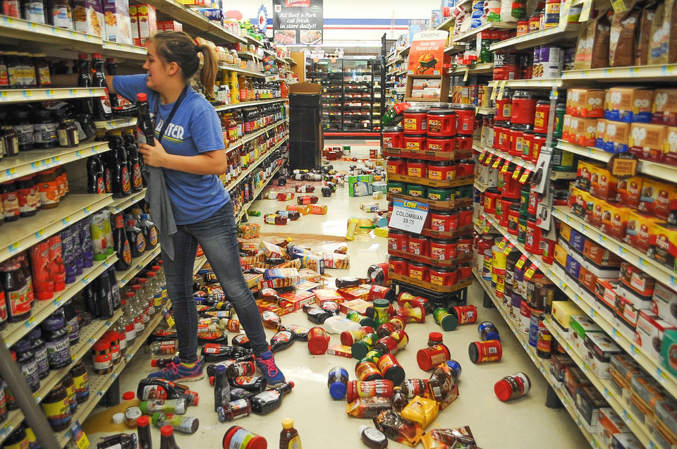 Photo - Store employee Talia Pershall, 16, places bottles of syrup back on a shelf while cleaning up at White's Foodliner grocery store in Pawnee, Okla., on Saturday, Sept. 3, 2016, following a 5.6 magnitude morning earthquake in north-central Oklahoma. The tremblor in the edge of the state's key energy-producing areas rattled the Midwest from Nebraska to North Texas. (David Bitton/The News Press via AP)