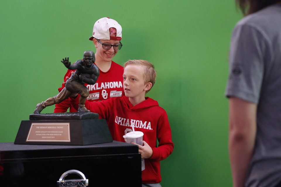 Photo - Kelsey Cooper, 17, and his brother Logan, 11, pose for a photo with the Heisman Trophy before a college football game between the University of Oklahoma Sooners (OU) and the West Virginia Mountaineers at Gaylord Family-Oklahoma Memorial Stadium in Norman, Okla, Saturday, Oct. 19, 2019. [Bryan Terry/The Oklahoman]