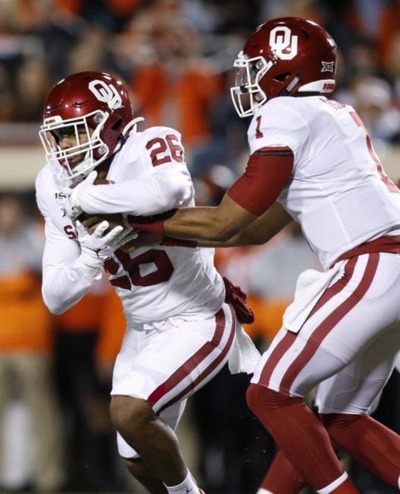 Photo -  Oklahoma's Jalen Hurts (1) hands the ball to Kennedy Brooks (26) during the Bedlam college football game between the Oklahoma State Cowboys (OSU) and Oklahoma Sooners (OU) at Boone Pickens Stadium in Stillwater, Okla., Saturday, Nov. 30, 2019. [Nate Billings/The Oklahoman]