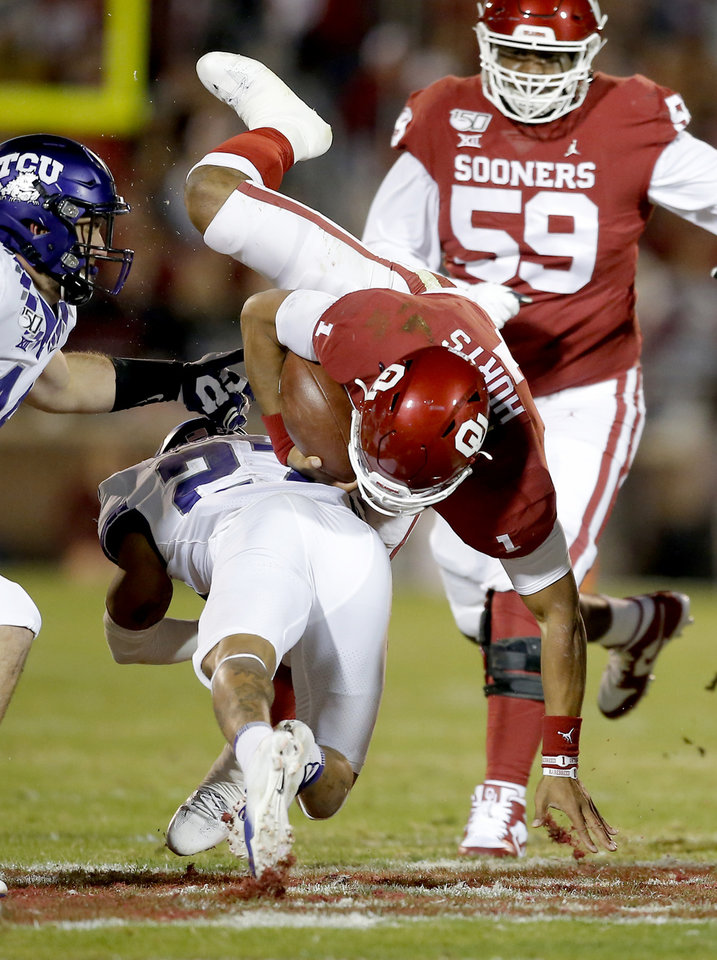 Photo - Oklahoma's Jalen Hurts (1) is tackled by Julius Lewis (24) in the first quarter  during an NCAA football game between the University of Oklahoma Sooners (OU) and the TCU Horned Frogs at Gaylord Family-Oklahoma Memorial Stadium in Norman, Okla., Saturday, Nov. 23, 2019. [Sarah Phipps/The Oklahoman]