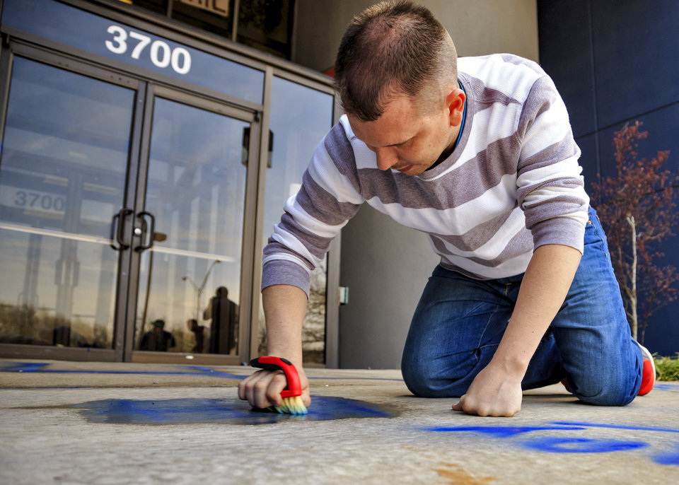 Photo - Volunteer Robert Chiles works to remove racist and homophobic symbols and language spray-painted on the building that includes the offices of the Oklahoma Democratic Party located at 3700 Classen Boulevard in Oklahoma City, Okla. on Thursday, March 28, 2019.  Photo by Chris Landsberger, The Oklahoman