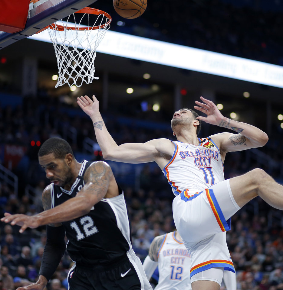 Photo - Oklahoma City's Abdel Nader (11) puts up a shot beside San Antonio's LaMarcus Aldridge (12) during an NBA basketball game between the Oklahoma City Thunder and the San Antonio Spurs at Chesapeake Energy Arena in Oklahoma City, Tuesday, Feb. 11, 2020. San Antonio won 114-106. [Bryan Terry/The Oklahoman]