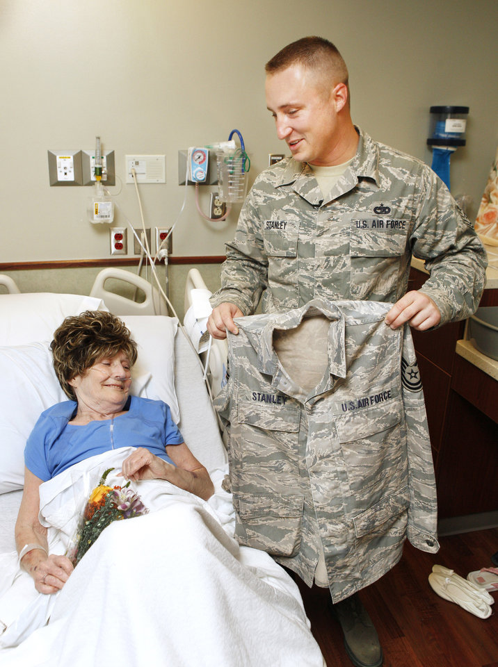 Photo - Tornado victim Sandra Adams returns an air force jacket to Air Force Tech. Sgt. Drew Stanley, 137th Air Refueling Wing, in her hospital room at Integris Southwest Medical Center in Oklahoma City Thursday, May 23, 2013. Stanley came upon Adams during rescue efforts after her home was destroyed by Monday's tornado and wrapped her in his Air Force jacket before she was taken to the hospital. Photo by Paul B. Southerland, The Oklahoman